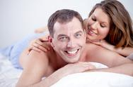 Happy man lying in bed with his wife, looking at camera and smiling Stock Photos