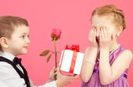 Little boy giving a rose and gift box to his girlfriend Stock Photos