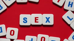 "Words ""SEX"" made of letters on a red background. Stop motion Stock Footage"