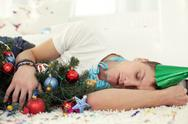 Young drunken man sleeping on floor with Christmas tree and in party hat Stock Photos