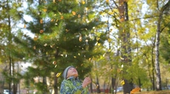 The child throws up over a yellow leaves in the park Stock Footage