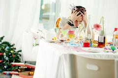 Young man sitting at messy table after turbulent party and trying to recollect t Stock Photos