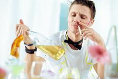 Young man drinking alcohol and smoking at party Stock Photos