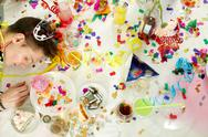 Messy table with confetti and alcohol and drunken man on it Stock Photos
