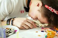 Young man sleeping with his face in cake at his birthday Stock Photos