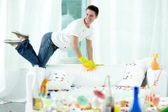Young man putting his room in order after violent party Stock Photos