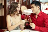 Young beautiful couple clinking glasses at restaurant Stock Photos