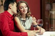 Young man whispering something to his girlfriend ear at restaurant Stock Photos