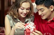 Young happy couple looking together at a small gift box Stock Photos