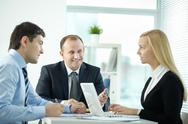 Three office workers discussing business issues in board room Stock Photos