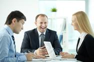 Three business people laughing while communicating at meeting Stock Photos