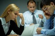 Three business people working late in office Stock Photos