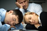 Three business people falling asleep at work Stock Photos