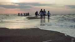Group of people walking on a sand spit in the Azov sea at sunset. HD Stock Footage
