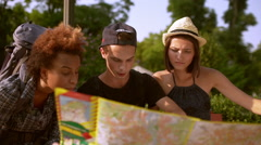 Tourists speaking looking for route at map sitting on bench in park Slow motion Stock Footage