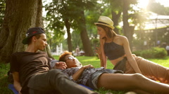 Friends travelers speaking lying on grass in park Slow motion Stock Footage