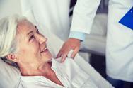 Doctor visiting happy senior woman at hospital Stock Photos