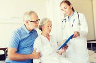 Senior woman and doctor with tablet pc at hospital Stock Photos