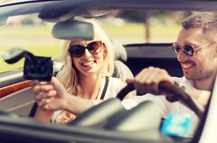 Happy couple usin gps navigation system in car Stock Photos