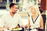 Happy couple eating dinner at restaurant terrace Stock Photos