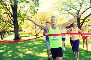 Happy young male runner winning on race finish Stock Photos