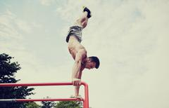 Young man exercising on parallel bars outdoors Stock Photos