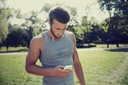 Young man with earphones and smartphone at park Stock Photos