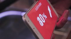 Hand holds smartphone, discounts on screen. Shopping mall black friday, sales Stock Footage