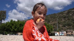 Wet after swim kid eats an apple Stock Footage