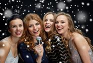 Happy young women with microphone singing karaoke Stock Photos