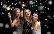 Happy young women with sparklers over snow Stock Photos