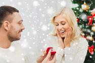 Man giving woman engagement ring for christmas Stock Photos