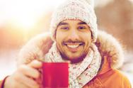 Happy man with tea cup outdoors in winter Stock Photos