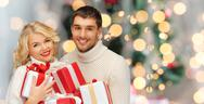 Happy couple in sweaters holding christmas gifts Stock Photos