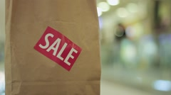 Brown paper bag with red sale sticker on it in shopping mall Close up Stock Footage