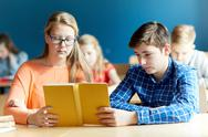 Students reading book at school lesson Stock Photos