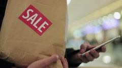 Man hold brown paper bag with SALE sticker on it in one hand and use smartphone Stock Footage