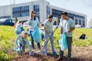 Volunteers with garbage bags cleaning park area Stock Photos