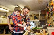 Father and son with chisel working at workshop Stock Photos