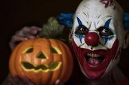 Evil clown with a carved pumpkin Stock Photos