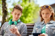 Teenage friends with gadgets outdoors Stock Photos