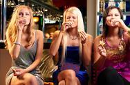 Three young girls drinking vodka at bar Stock Photos
