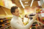 Young man choosing juice at supermarket Stock Photos