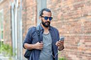Man with earphones and smartphone walking in city Stock Photos