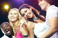 Four cheerful friends dancing at club Stock Photos