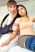 Unhappy couple with fractures at hospital Stock Photos