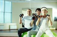 Three different males exercising with dumbbells in gym Stock Photos