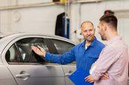 Auto mechanic with clipboard and man at car shop Stock Photos