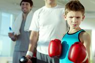 Little assertive boy looking at camera in boxing gloves against two men Stock Photos