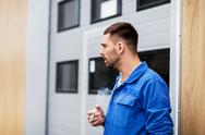 Auto mechanic smoking cigarette at car workshop Stock Photos